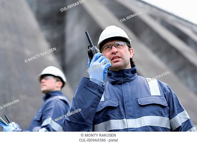 Worker using walkie talkie at foot of dam at hydroelectric power station
