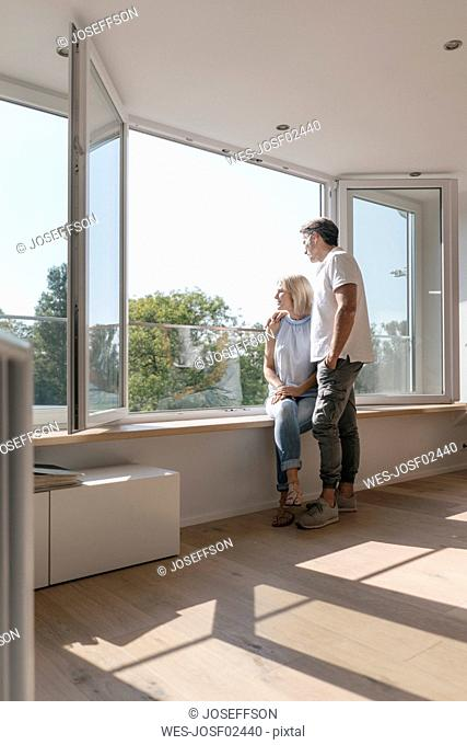 Mature couple at the window in empty room