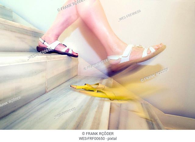 Woman slipping on banana peel on stairs
