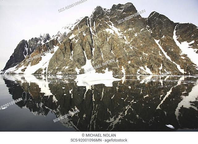 Reflections and snow covered mountains in the Lemaire Channel in Antarctica