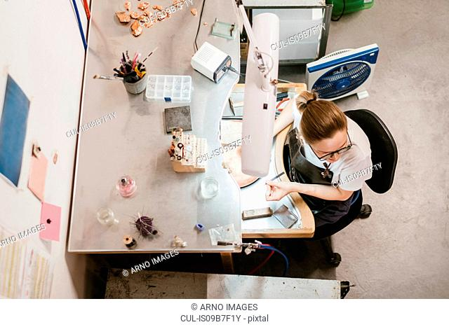 Overhead view of female jeweller at workbench