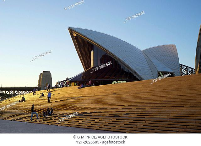 people on Sydney Opera House steps at sunset with Harbour Bridge in the background