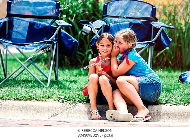 Two girls sitting on kerb, girl whispering into friends ear