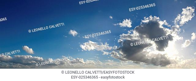 Blue sky with several cumulus clouds in background and a large cloud masking the sun, in the foreground, generating some godrays. Cinemascope format
