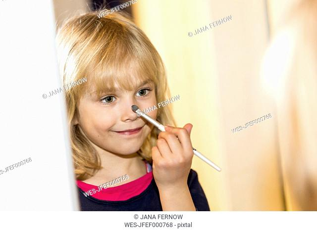 Mirror image of smiling little girl applying make up
