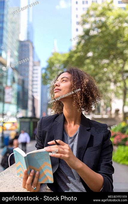 Contemplating Afro female professional with diary looking away in city