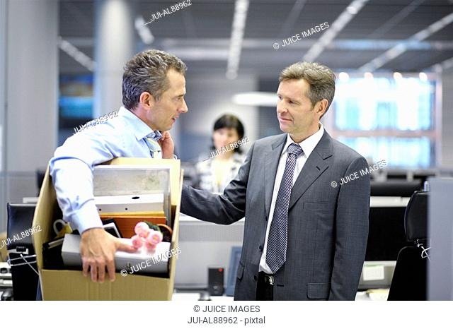 Businessman leaving office with box of personal items