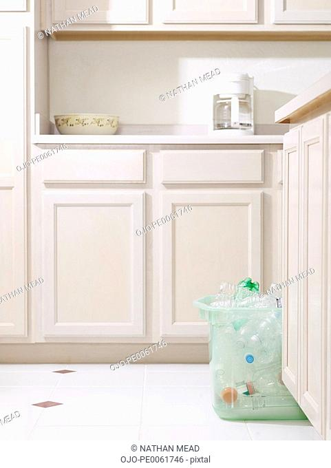 Bin of recyclable materials sitting on floor in kitchen