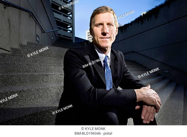 Caucasian businessman sitting on outdoor staircase