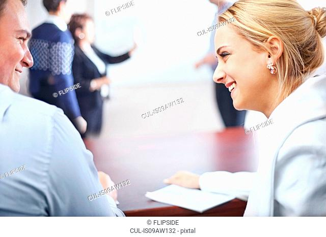 Over shoulder view of colleagues in conference room face to face smiling