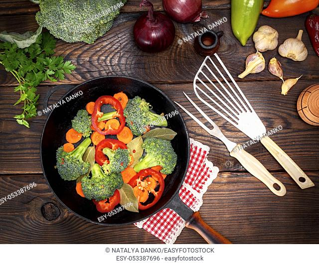 fresh vegetables in a black round frying pan on a brown wooden background, top view
