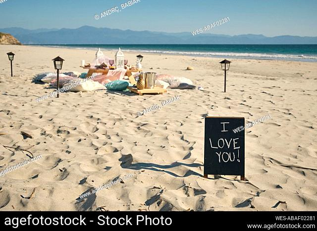 I LOVE YOU sign on placard near dining table at beach against clear blue sky during sunny day, Nayarit, Mexico