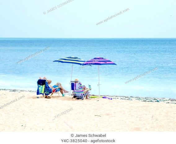 Couple relaxing on holiday under a beach umbrella on the Gulf of Mexico beach in Venice Florida USA