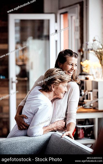 Cheerful young woman hugging grandmother while looking away