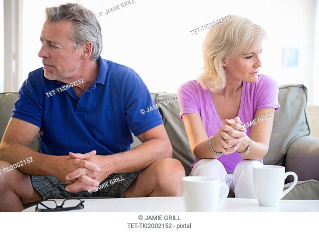 Portrait of couple sitting on sofa, looking away from each other