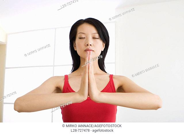 young woman doing yoga in prayer position