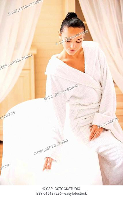 Time for bubble bath. Attractive young woman in bathrobe leaning at the bathtub and touching water with hand
