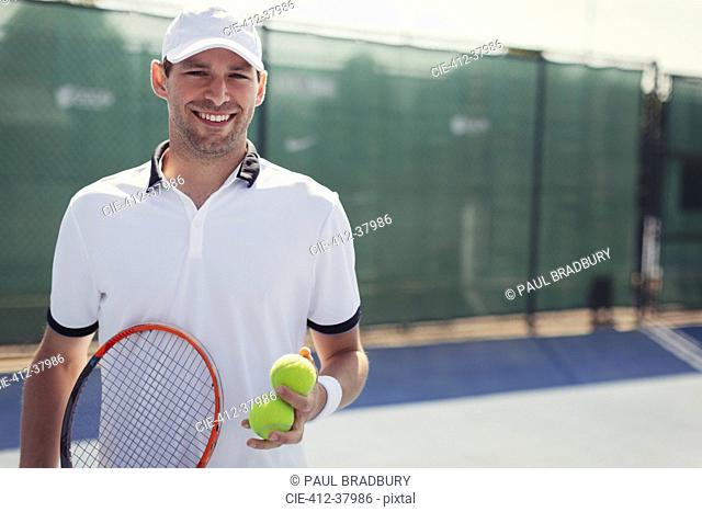 Portrait confident, smiling young male tennis player holding tennis racket and tennis balls on sunny tennis court