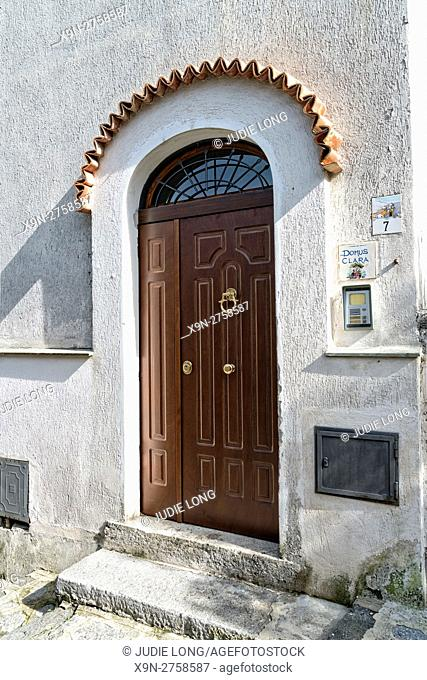 Beautiful Arched Entryway to a White Stucco Home, Stained Wooden Double Doors, Clay Tiles Covering the Upper Arch