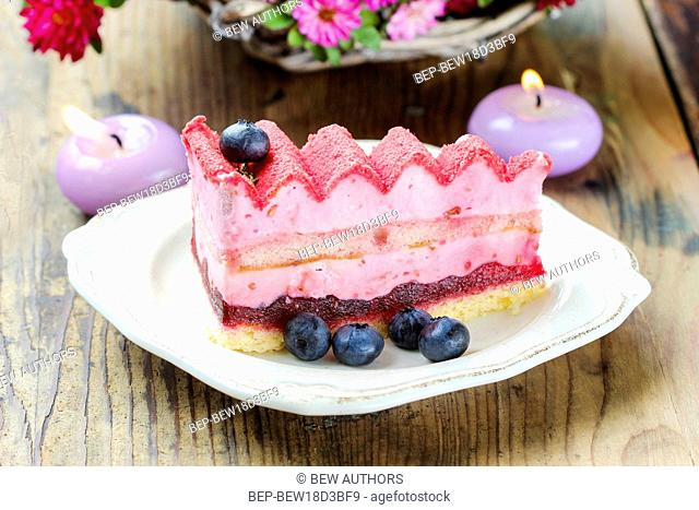 Pink layer cake decorated with fresh fruits on wooden table. Selective focus
