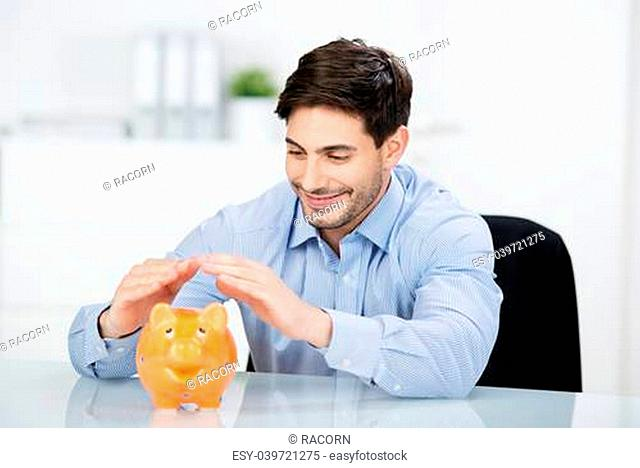 Conceptual portrait of happy young businessman covering piggybank