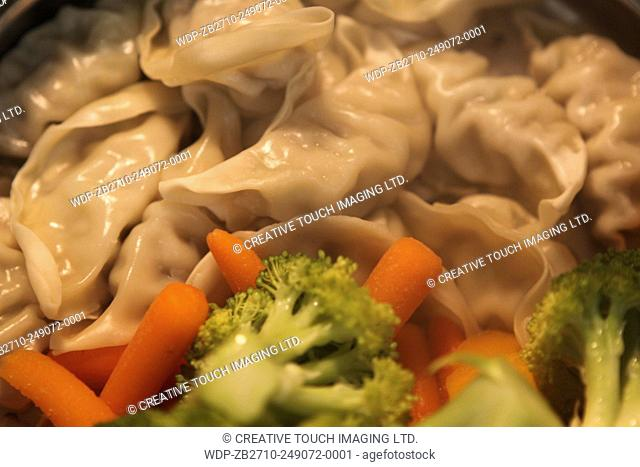 Dumplings and vegetables cooking in a steamer