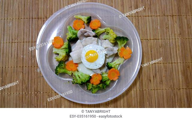 Fried quail egg with chicken, broccoli and carrots for the child