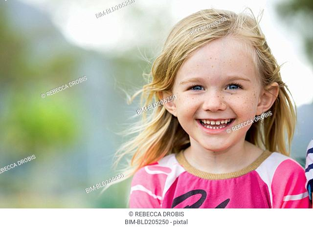 Smiling girl standing outdoors