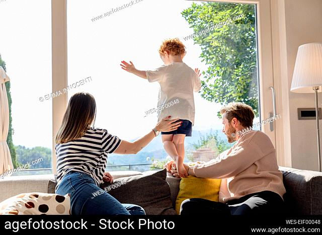 Parents and son looking out through window at home