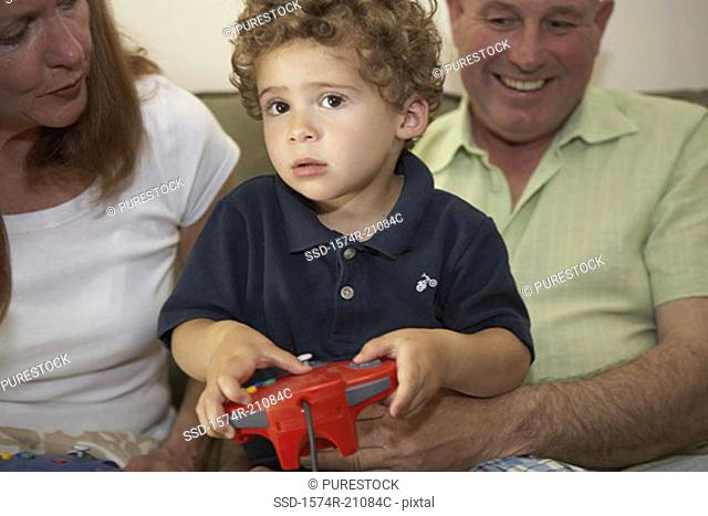 Close-up of a boy sitting with his grandparents and playing a video game