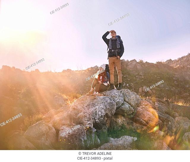 Young couple hiking, standing on rock