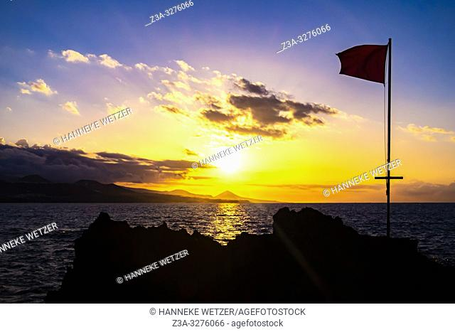 Sunset with flag at the coastline of Las Palmas de Gran Canaria, Canary Islands
