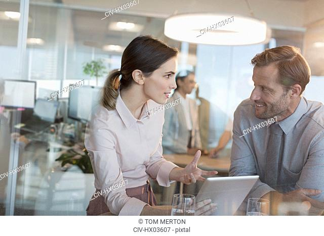 Businesswoman with digital tablet explaining to businessman in office meeting