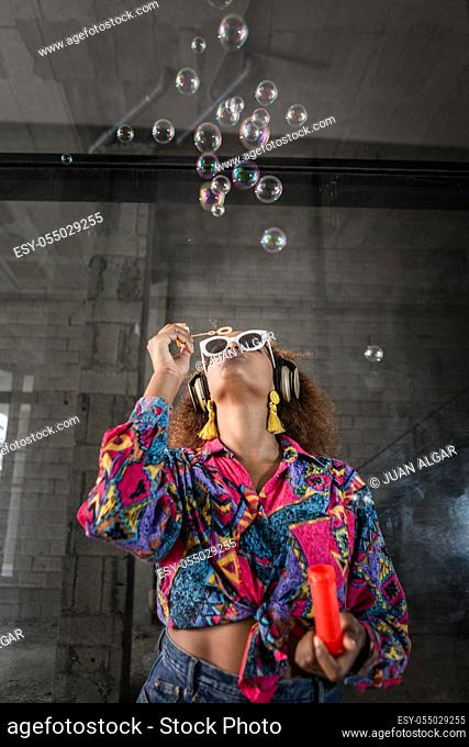 Trendy unrecognizable African American female in colorful blouse and earrings blowing transparent bubbles while looking up standing in sunglasses and headphones...