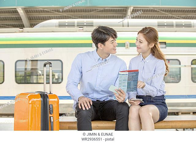 Young smiling couple travelers at station