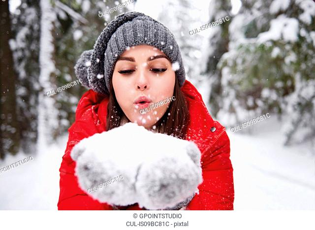 Young woman blowing snowflakes off hands