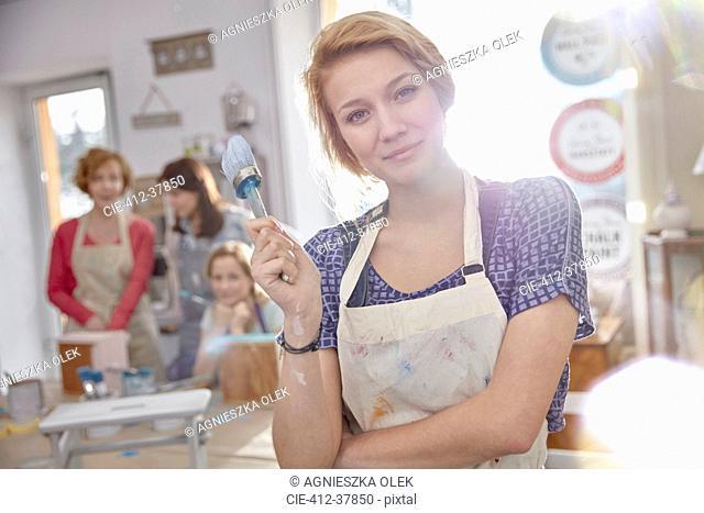 Portrait confident female artist painting in art class workshop