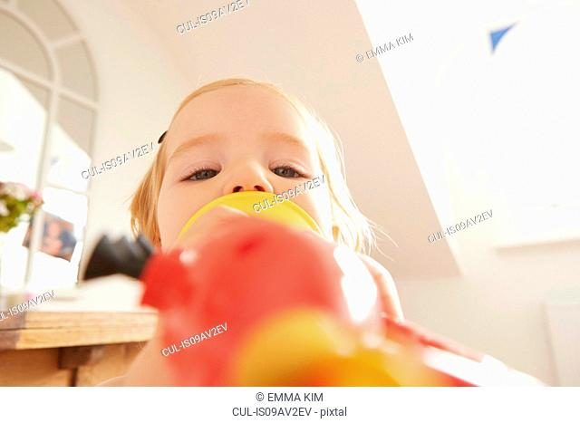 Close up of female toddler playing toy trumpet