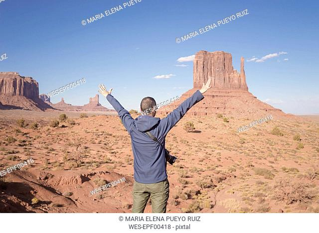 USA, Utah, back view of man with raised arms looking at Monument Valley