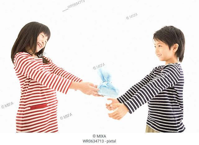 Girl holding out box to boy