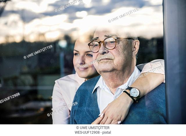 Portrait of young woman embracing senior man at the window