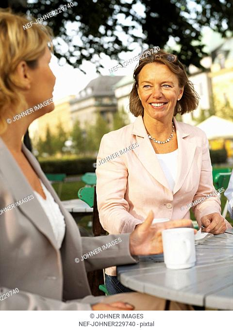 Two women having a coffee outdoors