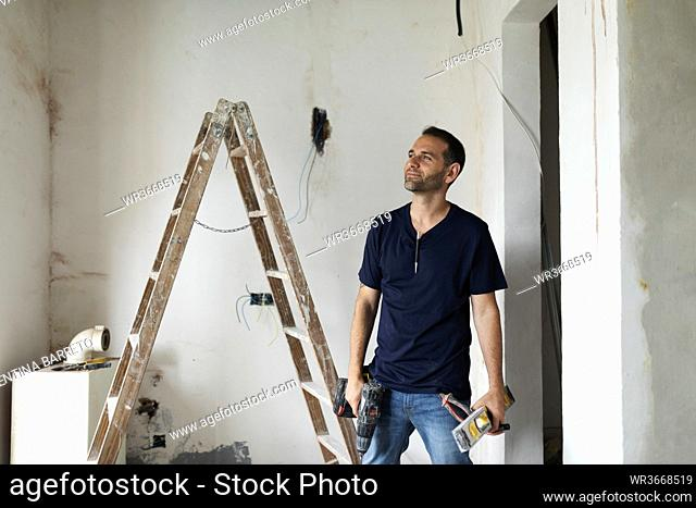 Confident construction worker standing in a house under construction