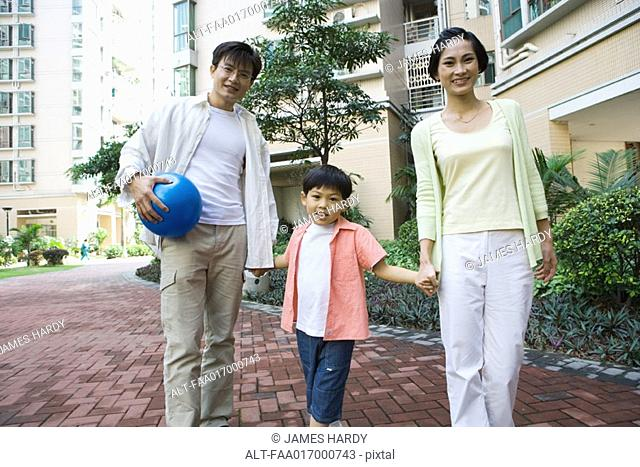 Family standing by apartment complex, smiling at camera, father holding ball