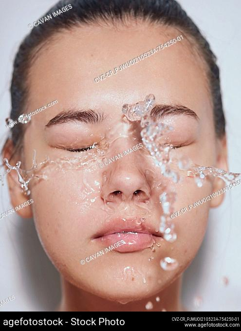 Young beautiful woman with clean fresh skin with splash of water - white background