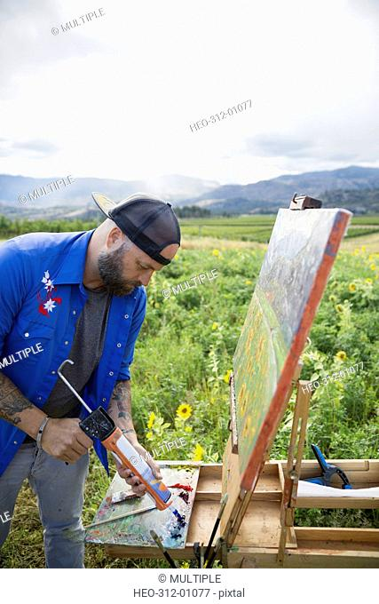 Male painter squeezing paint onto palette in rural field