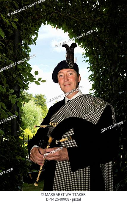 Piper dressed in traditional Northumbrian tartan playing Northumbrian smallpipes; Alnwick, Northumberland, England
