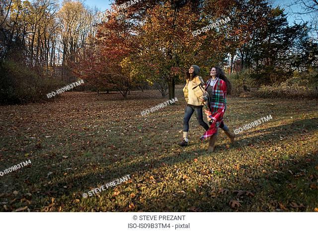 Two female friends striding across autumn park