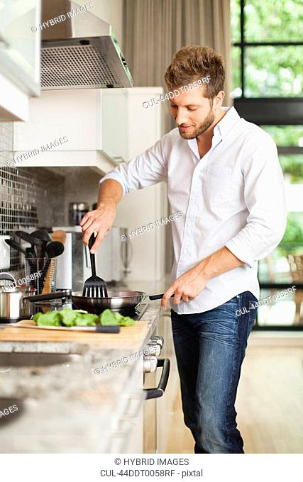 Smiling man cooking in kitchen