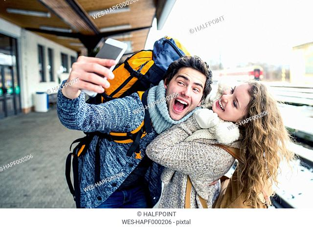Playful young couple on station platform taking a selfie